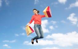 Mujer joven sonriente con el salto de los panieres Imagen de archivo libre de regalías