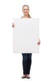 Mujer joven sonriente con el tablero en blanco blanco Fotos de archivo libres de regalías
