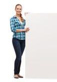 Mujer joven sonriente con el tablero en blanco blanco Imágenes de archivo libres de regalías