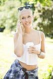 Mujer joven sonriente con el teléfono y el café en parque Fotos de archivo libres de regalías