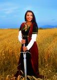 Mujer joven sonriente con el vestido ornamental y Fotografía de archivo
