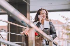 Mujer joven sonriente con la bicicleta que habla en el teléfono móvil imagen de archivo libre de regalías