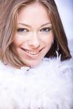 Mujer joven sonriente con la boa azul del ojo y blanca imagenes de archivo