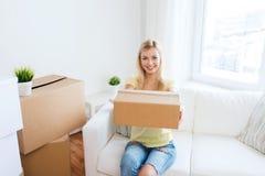 Mujer joven sonriente con la caja de cartón en casa Foto de archivo