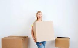 Mujer joven sonriente con la caja de cartón en casa Fotografía de archivo libre de regalías