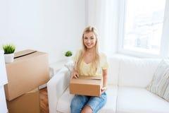 Mujer joven sonriente con la caja de cartón en casa Foto de archivo libre de regalías