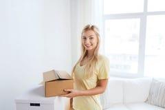 Mujer joven sonriente con la caja de cartón en casa Fotos de archivo libres de regalías