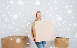 Mujer joven sonriente con la caja de cartón en casa Imagen de archivo libre de regalías