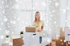 Mujer joven sonriente con la caja de cartón en casa Fotos de archivo