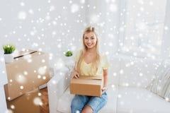 Mujer joven sonriente con la caja de cartón en casa Imagen de archivo