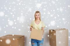 Mujer joven sonriente con la caja de cartón en casa Imágenes de archivo libres de regalías