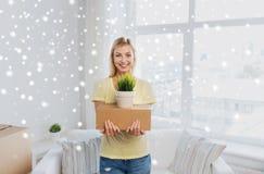 Mujer joven sonriente con la caja y la planta en casa Imágenes de archivo libres de regalías