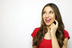 Mujer joven sonriente con la camiseta roja que mira al lado que desea una cierta cosa en el fondo blanco Copie el espacio Imagenes de archivo
