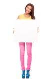 Mujer joven sonriente con la cartelera en blanco Foto de archivo libre de regalías
