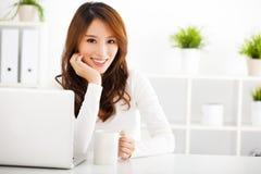 Mujer joven sonriente con la computadora portátil Fotografía de archivo libre de regalías
