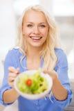 Mujer joven sonriente con la ensalada verde en casa Imágenes de archivo libres de regalías