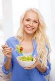 Mujer joven sonriente con la ensalada verde en casa Imagen de archivo libre de regalías