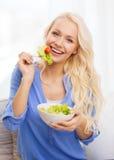 Mujer joven sonriente con la ensalada verde en casa Fotos de archivo