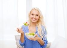 Mujer joven sonriente con la ensalada verde en casa Imagen de archivo