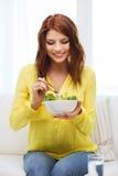 Mujer joven sonriente con la ensalada verde en casa Fotos de archivo libres de regalías
