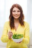 Mujer joven sonriente con la ensalada verde en casa Foto de archivo