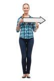 Mujer joven sonriente con la flecha poiting Imagen de archivo libre de regalías