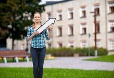 Mujer joven sonriente con la flecha poiting para arriba Foto de archivo libre de regalías