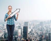 Mujer joven sonriente con la flecha poiting para arriba Imágenes de archivo libres de regalías