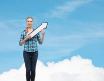 Mujer joven sonriente con la flecha poiting para arriba Imagen de archivo