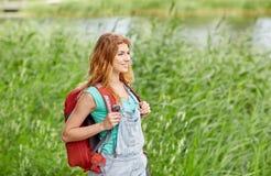 Mujer joven sonriente con la mochila que camina en bosque Fotografía de archivo libre de regalías