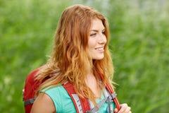 Mujer joven sonriente con la mochila que camina en bosque Imagenes de archivo