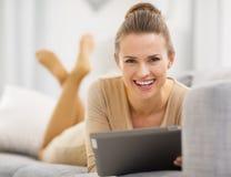 Mujer joven sonriente con la PC de la tableta que pone en el sofá Foto de archivo