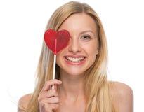 Mujer joven sonriente con la piruleta en forma de corazón Fotografía de archivo