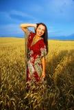 Mujer joven sonriente con la situación ornamental del vestido Imágenes de archivo libres de regalías