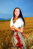 Mujer joven sonriente con la situación ornamental del vestido Imagen de archivo libre de regalías