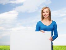Mujer joven sonriente con la tarjeta blanca en blanco Imagen de archivo libre de regalías