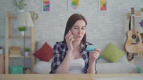 Mujer joven sonriente con la tarjeta de crédito a disposición que habla en el teléfono en un apartamento moderno almacen de metraje de vídeo
