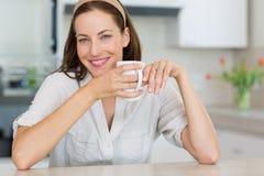 Mujer joven sonriente con la taza de café en la cocina Foto de archivo