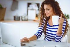 Mujer joven sonriente con la taza de café y el ordenador portátil en la cocina en casa Mujer joven sonriente Imagen de archivo
