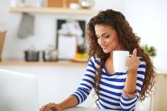 Mujer joven sonriente con la taza de café y el ordenador portátil en la cocina en casa Mujer joven sonriente Fotos de archivo