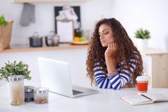 Mujer joven sonriente con la taza de café y el ordenador portátil en la cocina en casa Mujer joven sonriente Foto de archivo