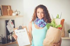Mujer joven sonriente con la taza de café y el ordenador portátil en la cocina en casa Mujer joven sonriente Foto de archivo libre de regalías