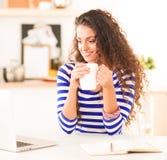 Mujer joven sonriente con la taza de café y el ordenador portátil en la cocina en casa Mujer joven sonriente Imagen de archivo libre de regalías