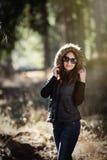 Mujer joven sonriente con las gafas de sol en bosque Imagen de archivo