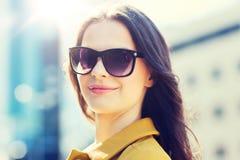 Mujer joven sonriente con las gafas de sol en ciudad Imagen de archivo libre de regalías