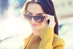 Mujer joven sonriente con las gafas de sol en ciudad Imágenes de archivo libres de regalías