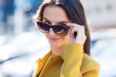 Mujer joven sonriente con las gafas de sol en ciudad Imagenes de archivo