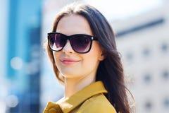Mujer joven sonriente con las gafas de sol en ciudad Fotos de archivo libres de regalías
