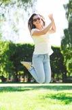 Mujer joven sonriente con las gafas de sol en parque Imágenes de archivo libres de regalías