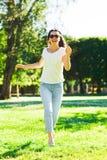 Mujer joven sonriente con las gafas de sol en parque Fotos de archivo libres de regalías